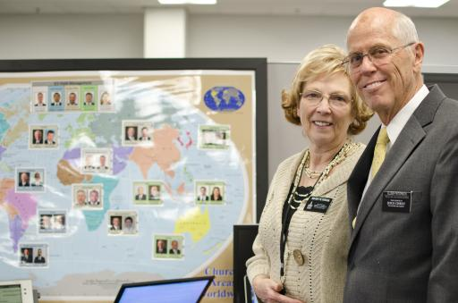 Petersons standing side by side in front of their global map for senior missionaries